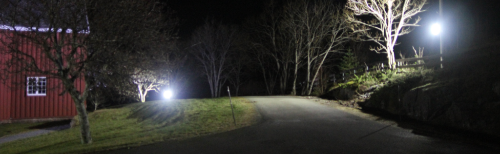 lyskaster som lyser opp en kirke fra avstand