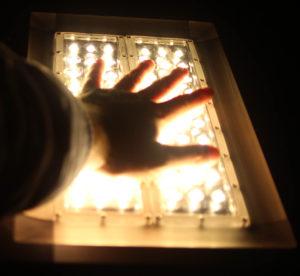 en hånd som legges på et LED flomlys