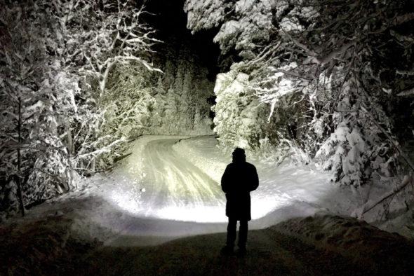 bilde av en person i norge på vinteren som lyser opp en vei med en hodelykt
